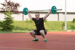 Young Man Doing A Overhead Squat Exercise Outdoor - stock photo