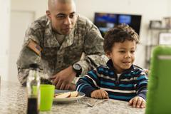 Mixed race soldier father and son eating in kitchen - stock photo