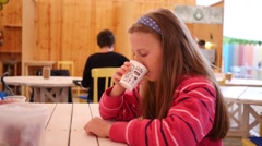 Cute teen school age girl tastes drinks coffee first time in life - stock footage