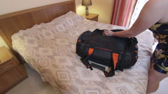 Woman traveler unpacking travel bag on bed in hotel room Stock Footage