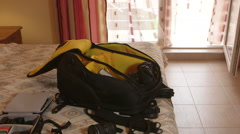 Unpacked professional photo camera backpack on bed in hotel room - stock footage
