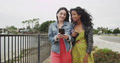 Cute girlfriends walking by the river linking arms Stock Footage