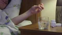 Woman on bed in bedroom taking sleeping pills on bedside table Stock Footage