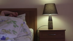 Woman in bed turns off light lamp on bedside table and falls asleep Stock Footage