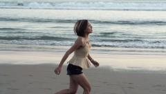 Young woman running along beach, slow motion shot at 240fps HD Stock Footage