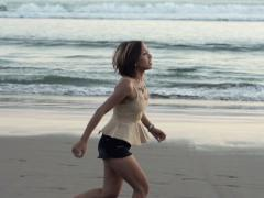 Young woman running along beach, slow motion shot at 240fps NTSC Stock Footage