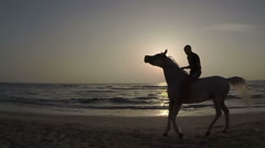 Rider on horseback at sunset and the sea. Stock Footage