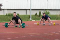 Young People Doing A Overhead Squat Exercise Outdoor - stock photo