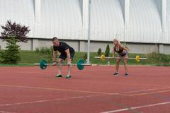 Young People Doing Bent Over Barbell Row Exercise - stock photo