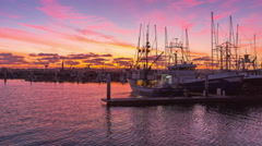 A Time-Lapse Of Gorgeous Painted Skies Over A Coastal Boat Harbor. Stock Footage