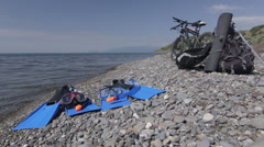 Two bicycles and snorkeling sets on wild pebble beach Stock Footage