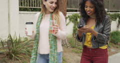 Happy friends walkind together using smartphone Stock Footage