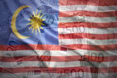 Stock Photo of colorful waving malaysian flag on a euro money background