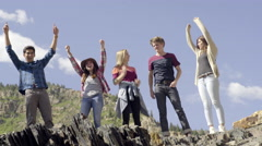 Fun Group Of Teens Reach The Top Of Mountain Peak, They High Five And Hug (4K) Stock Footage