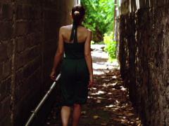 Woman walking through narrow path NTSC Stock Footage