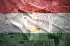 colorful waving tajikistan flag on a euro money background - stock photo