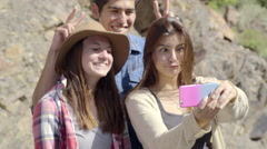 Happy Teens On A Mountain, Take Selfie Together, Boy Gives Girls Bunny Ears (4K) Stock Footage