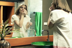 Beautiful woman cleaning face with cotton swab in the bathroom at home NTSC Stock Footage