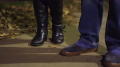 Two pairs of feet walking down a sidewalk at night - stock footage