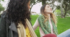Bestfriends sitting outdoors telling each other stories Stock Footage