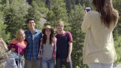 Teen Takes Photos Of Her Friends On A Mountain, Her Friends Turn And Wave Stock Footage