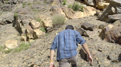 Excited Teenage Boy Scrambles Up Rocky Slope (4K) Stock Footage