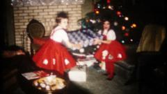2256 - young girls pass out Christmas gifts at home - vintage film home movie Stock Footage