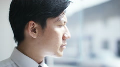 4k, Portrait of young, asian businessman looking serious into camera - stock footage