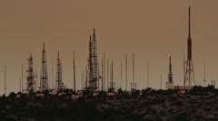 Cell/broadcast towers and radars site on mountain top at dusk Stock Footage