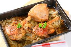 Roast duck legs with caraway and onion in a baking pan Stock Photos