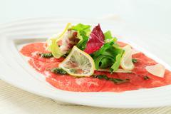 Beef Carpaccio with pesto, salad greens and Parmesan Stock Photos