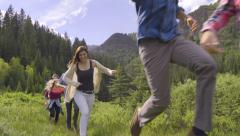 Wild And Free Teens Run, Jump And Twirl Through Mountain Meadow (Slow Motion) Stock Footage