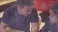 A young couple holding hands at a restaurant and laughing, through the window - stock footage