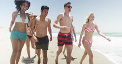 Fun young adult group of multi ethnic friends walking the beach - stock footage
