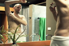 Young man in towel applying antiperspirant on his armpit in bathroom  NTSC Stock Footage