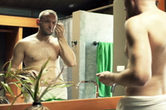 Young man in towel applying anti wrinkle roll-on on his face in bathroom NTSC - stock footage
