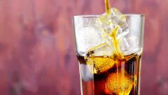 Pouring fresh coke with ice cubes on wood background Stock Footage