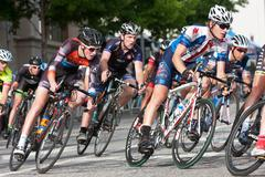 Tight Pack Of Cyclists Lean Into Turn In Amateur Race - stock photo