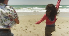 Group of young multi ethnic friends running into water at the beach - stock footage