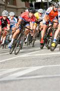 Male Cyclists Lean Into Turn In Amateur Bike Race - stock photo