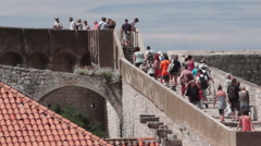 Tourists exploring the city walls around Dubrovnik Croatia Stock Footage
