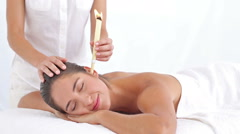 Beautiful woman receiving ear candle treatment at spa center Stock Footage
