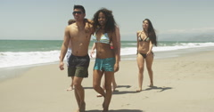 Group of young adult interracial friends running slow motion on the beach - stock footage