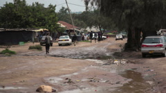 People walk on bad road infrastructure in African town, Maralal, Kenya, Samburu Stock Footage