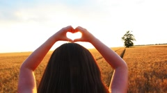 Heart-Shape with Hands in Sunset in Wheat Filed Stock Footage