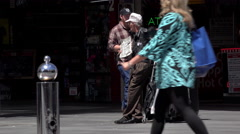 Homeless elderly man standing on Fremont street with sign 4k - stock footage