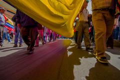Street view from under giant ecuadorian flag during anti government march and Stock Photos