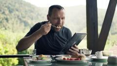Young man reading news on tablet computer and eating breakfast on terrace HD Stock Footage