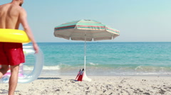 Happy man lying on the beach with rubber ring Stock Footage