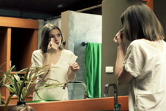 Young woman applying anti wrinkle roll-on on her face in bathroom  NTSC Stock Footage